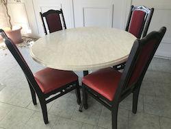 Table ronde avec 4 chaises rouges et noires dans une salle de restaurant vide